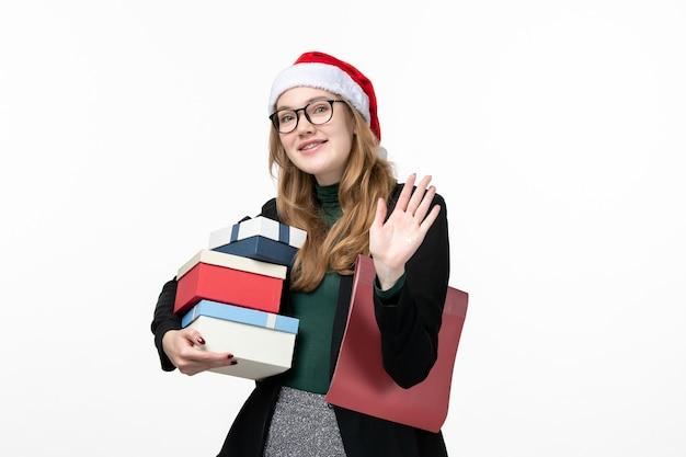 Mulher jovem segurando presentes de férias na parede branca livro aula faculdade