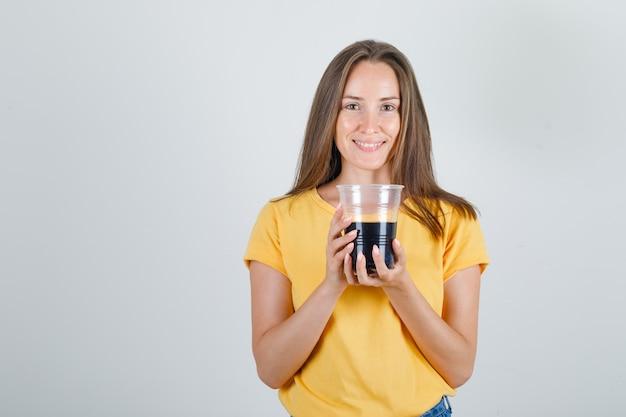 Mulher jovem segurando refrigerante em copo em camiseta, shorts e parecendo alegre