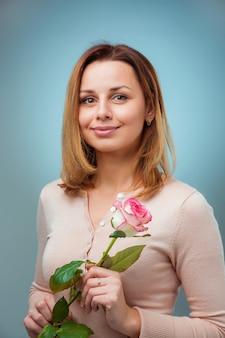 Mulher jovem, segurando, rosa, e, sorrindo