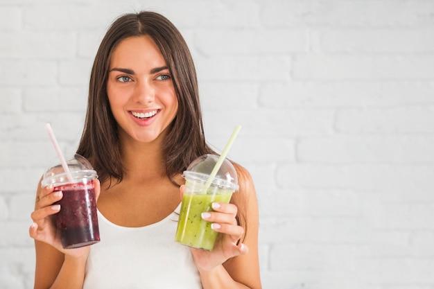 Mulher jovem, segurando, smoothies, em, copo plástico