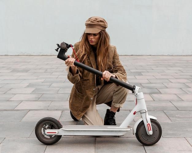 Mulher jovem segurando sua scooter elétrica