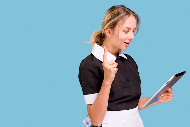 Mulher jovem, segurando, tablete digital, com, apontar, cima, contra, experiência azul