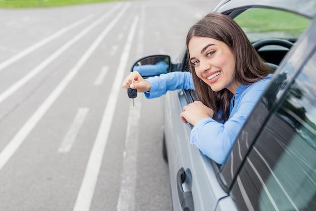 Mulher jovem, segurando, teclas, para, carro novo, e, sorrindo, câmera