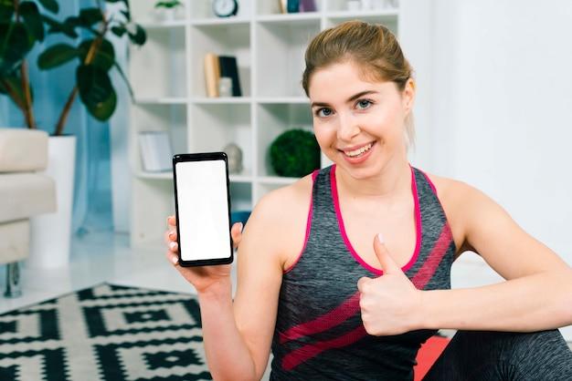 Mulher jovem, segurando, telefone móvel, com, branca, tela, exposição, mostrando, polegar, sinal