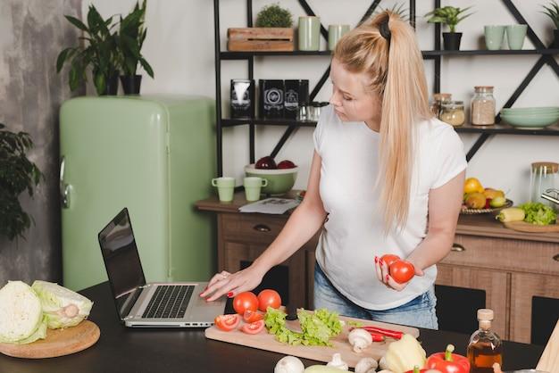 Mulher jovem, segurando, tomates vermelhos, em, mão, usando computador portátil, cozinha