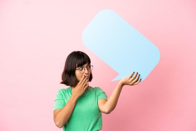 Mulher jovem segurando um balão de fala vazio com expressão de surpresa