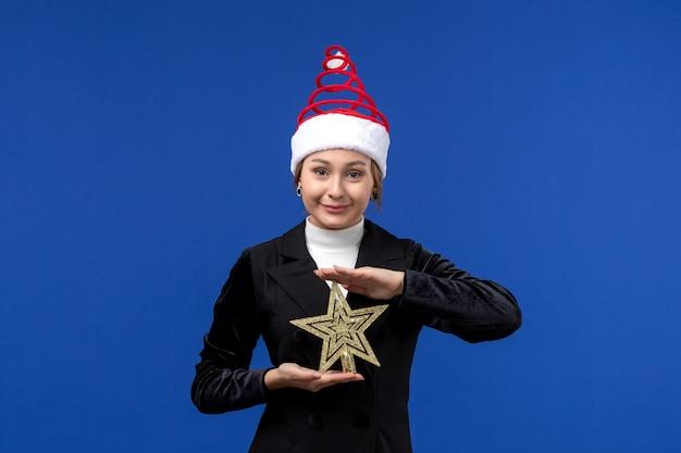 Mulher jovem segurando um brinquedo em forma de estrela de frente na mesa azul, feriado de véspera de ano novo