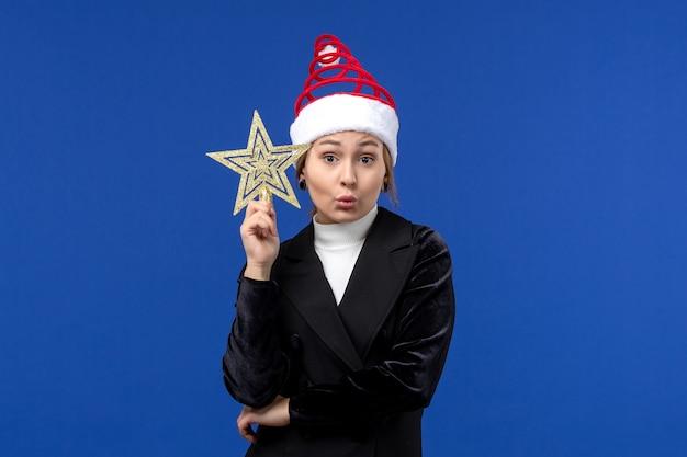 Mulher jovem segurando um brinquedo em forma de estrela de frente na parede azul, feriado de véspera de ano novo