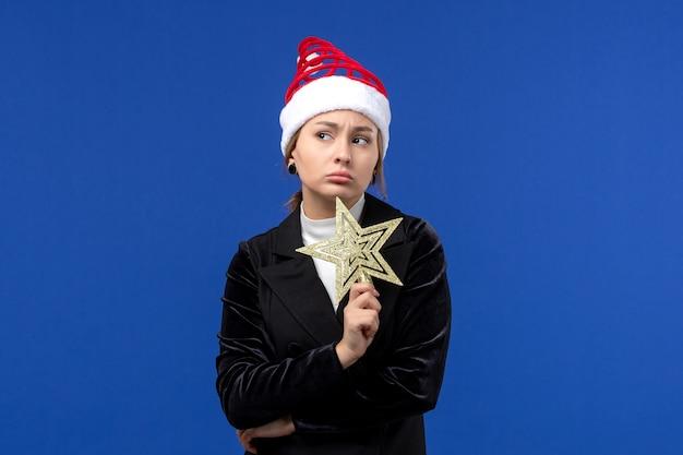 Mulher jovem segurando um brinquedo em forma de estrela de frente na parede azul, feriados de véspera de ano novo