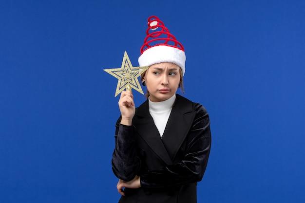 Mulher jovem segurando um brinquedo em forma de estrela de frente na parede azul feriados véspera de ano novo