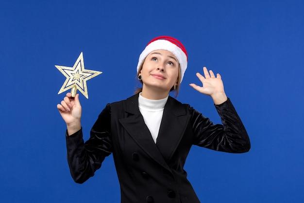 Mulher jovem segurando um brinquedo em forma de estrela de frente no fundo azul, feriado de véspera de ano novo
