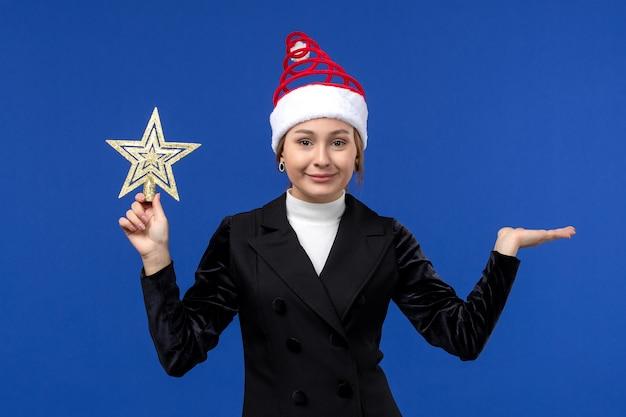 Mulher jovem segurando um brinquedo em forma de estrela de frente no fundo azul mulher de feriados de ano novo