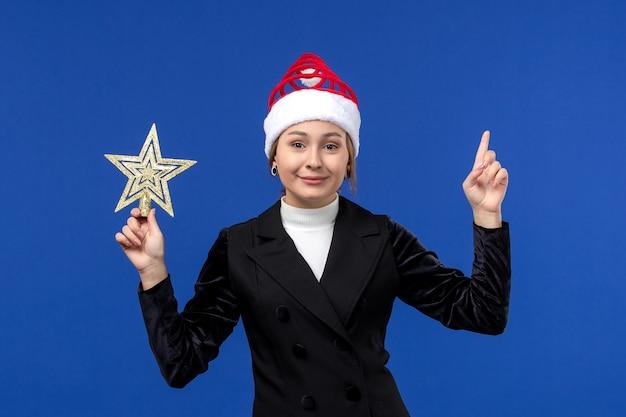 Mulher jovem segurando um brinquedo em forma de estrela de frente no fundo azul mulher feriados ano novo