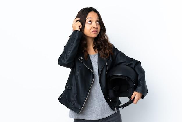Mulher jovem segurando um capacete de motocicleta sobre um branco isolado, tendo dúvidas e pensando