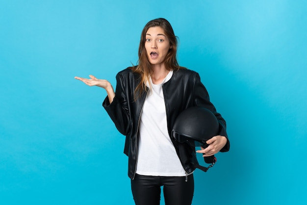 Mulher jovem segurando um capacete de motociclista isolado em uma parede azul com expressão facial chocada