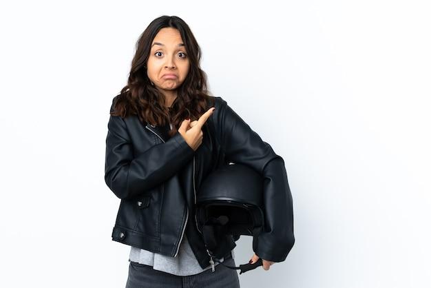 Mulher jovem segurando um capacete de motociclista sobre uma parede branca isolada apontando para as laterais, tendo dúvidas