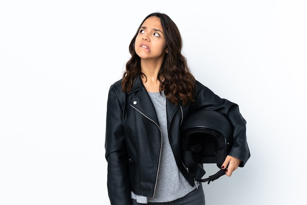 Mulher jovem segurando um capacete de motociclista sobre uma parede branca isolada com expressão confusa