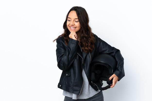 Mulher jovem segurando um capacete de motociclista sobre uma parede branca isolada, olhando para o lado