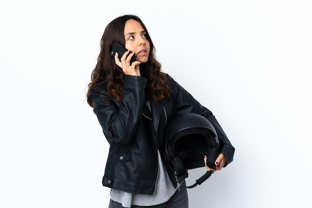 Mulher jovem segurando um capacete de motociclista sobre uma parede branca isolada, segurando um café para levar e um móbile
