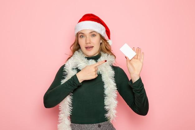 Mulher jovem segurando um cartão de banco branco na parede-de-rosa modelo de emoção férias de frente