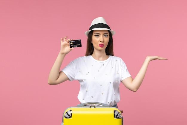 Mulher jovem segurando um cartão de banco preto na parede rosa viagem de cor de frente