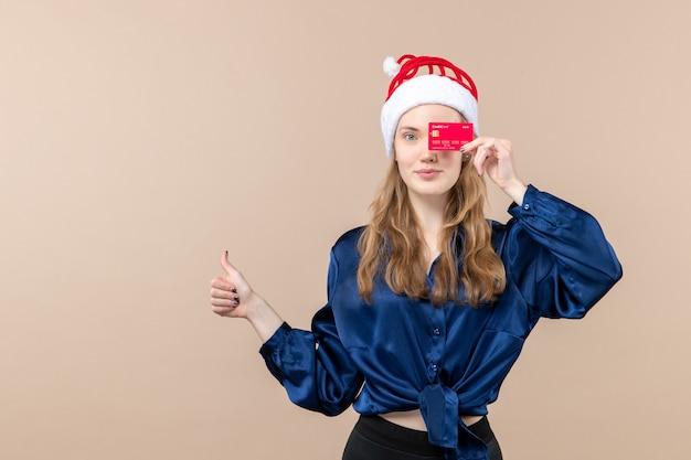 Mulher jovem segurando um cartão de banco vermelho em um fundo rosa, ano novo, feriado, foto, emoção, frontal