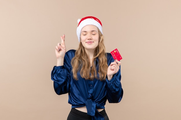 Mulher jovem segurando um cartão de banco vermelho em um fundo rosa.