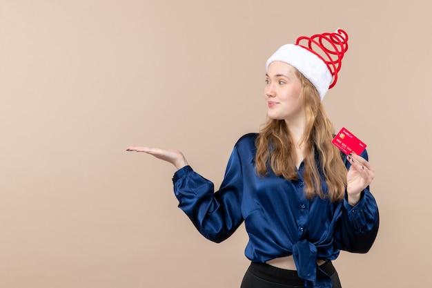 Mulher jovem segurando um cartão de banco vermelho no fundo rosa foto de férias de dinheiro de frente ano novo espaço livre de emoção de natal