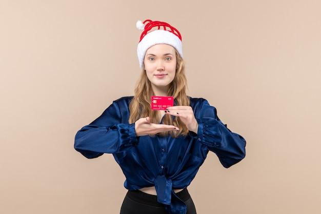Mulher jovem segurando um cartão de banco vermelho sobre um fundo rosa. foto de férias ano novo emoção natal dinheiro