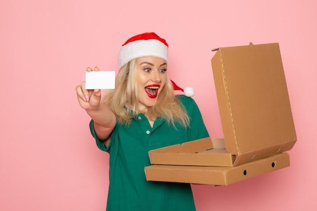 Mulher jovem segurando um cartão do banco e caixas de pizza na cor rosa da parede de frente, feriado de natal, ano novo, foto trabalho uniforme