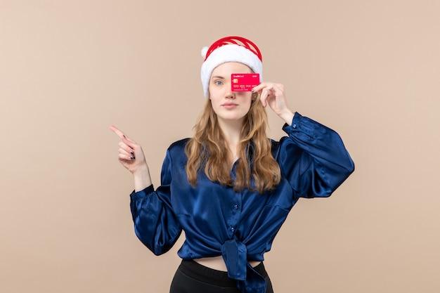 Mulher jovem segurando um cartão vermelho no fundo rosa, férias natal, dinheiro, fotos, vista frontal, ano novo, emoção