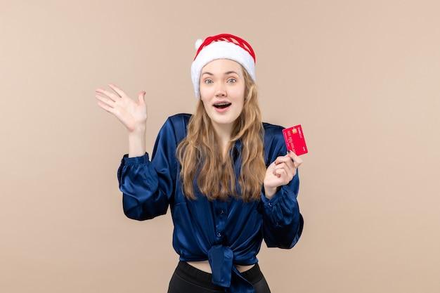 Mulher jovem segurando um cartão vermelho no fundo rosa. foto do dinheiro do natal