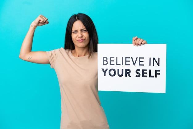 Mulher jovem segurando um cartaz com o texto acredite em si mesmo e fazendo gestos firmes em um fundo isolado.