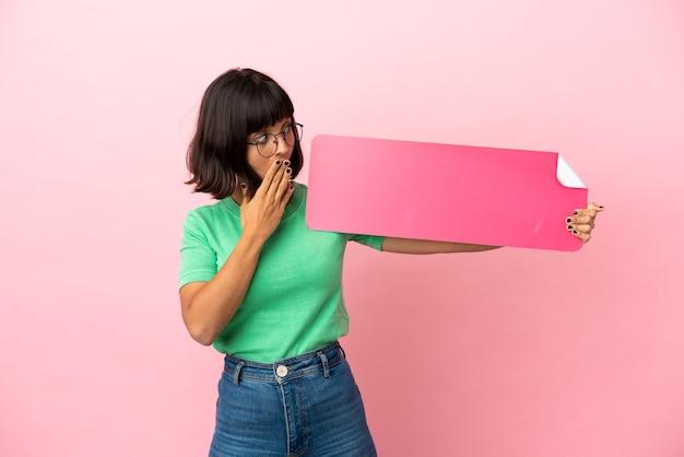 Mulher jovem segurando um cartaz vazio com expressão de surpresa