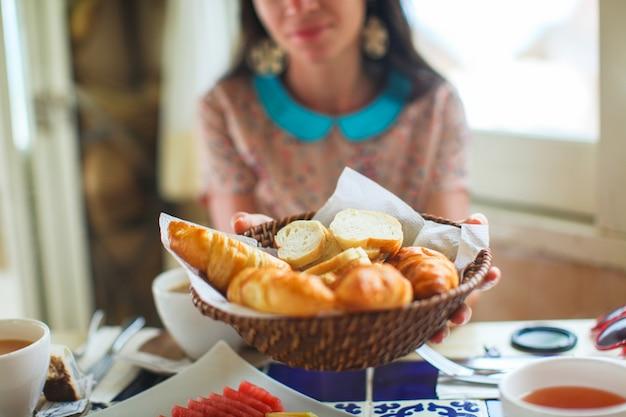 Mulher jovem, segurando, um, cesta, de, croissants, em, a, praia, restaurante