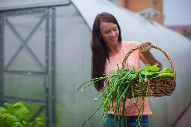 Mulher jovem, segurando, um, cesta, de, verdura, e, cebola, em, a, estufa