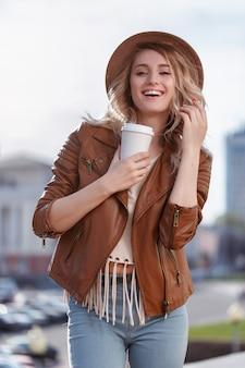 Mulher jovem segurando um copo de papel com café
