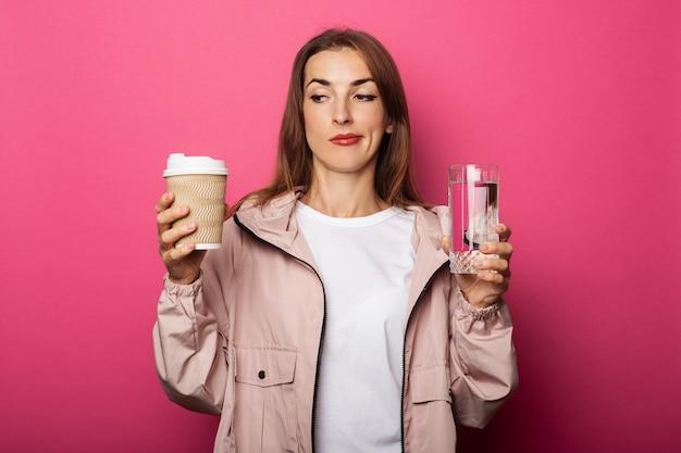 Mulher jovem segurando um copo de papel e um copo de vidro com água