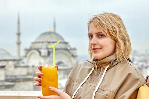 Mulher jovem segurando um copo de suco em frente à mesquita, do lado de fora da janela