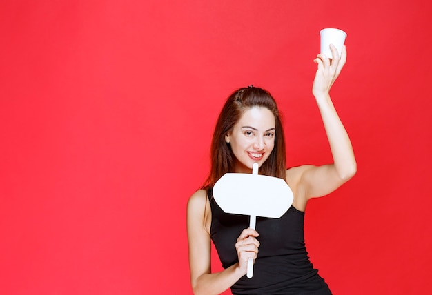 Mulher jovem segurando um copo descartável de bebida e uma mesa de informações branca