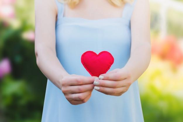 Mulher jovem, segurando, um, coração vermelho, em, dela, mãos