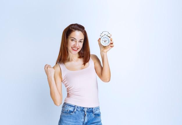 Mulher jovem segurando um despertador e se sentindo bem-sucedida