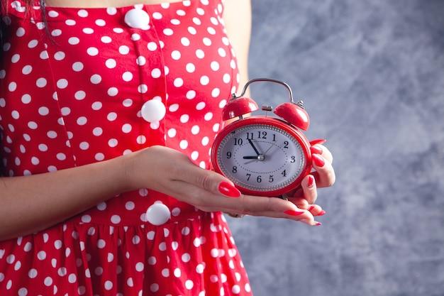 Mulher jovem segurando um despertador