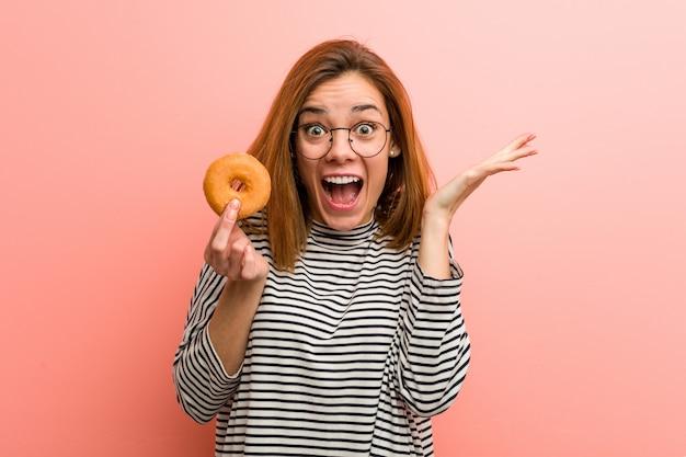 Mulher jovem, segurando, um, donut, celebrando, um, vitória, ou, sucesso