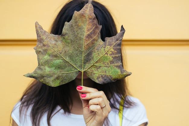 Mulher jovem, segurando, um, folha caída, em, a, rosto, durante, um, outono, passeio, ao ar livre