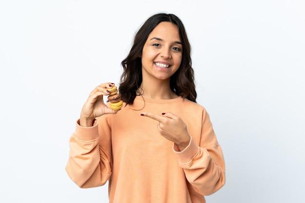 Mulher jovem segurando um fundo branco isolado segurando macarons franceses coloridos e apontando para ele