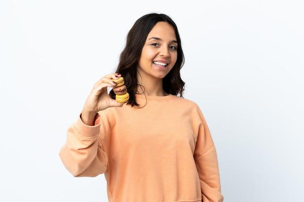 Mulher jovem segurando um fundo branco isolado, segurando macarons franceses coloridos e com uma expressão feliz