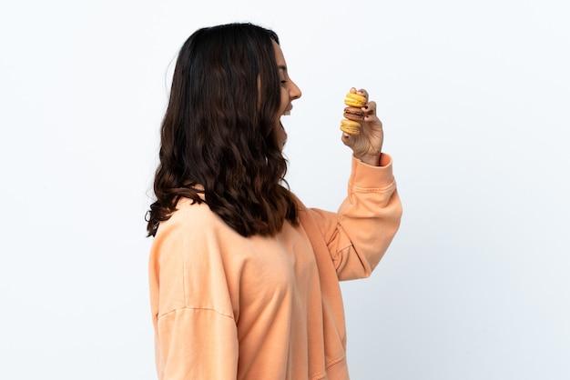 Mulher jovem segurando um fundo branco isolado segurando macarons franceses coloridos e comendo