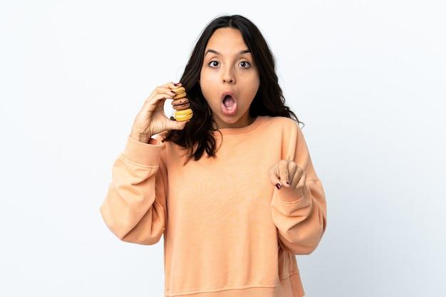 Mulher jovem segurando um fundo branco isolado segurando macarons franceses coloridos e se surpreendendo ao apontar para a frente