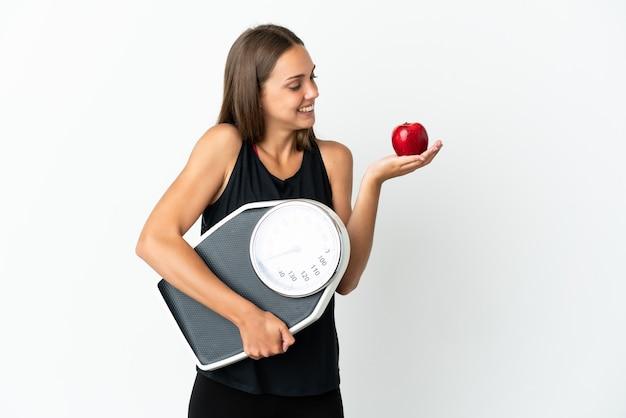 Mulher jovem segurando um fundo branco isolado segurando uma balança enquanto olha para uma maçã
